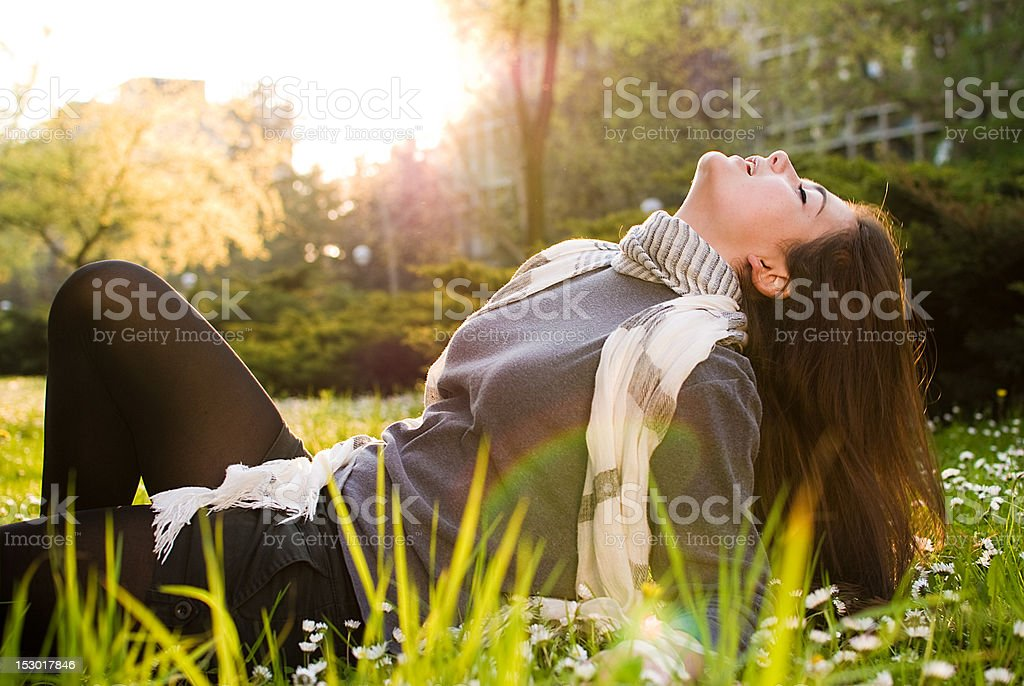 Lovely girl laying on the grass and enjoying in sunshine royalty-free stock photo