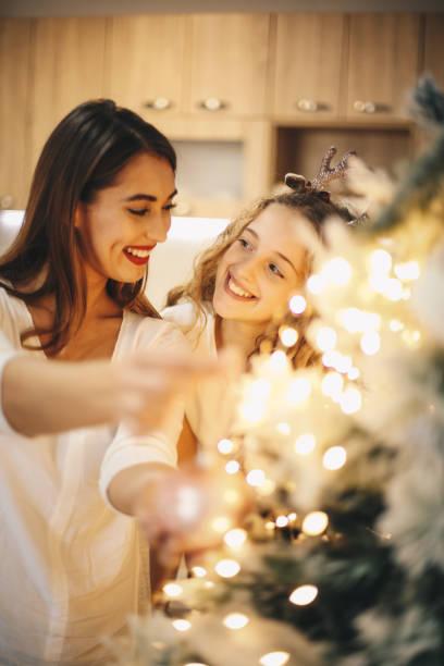 Lovely girls enjoying while decorating Christmas tree. stock photo