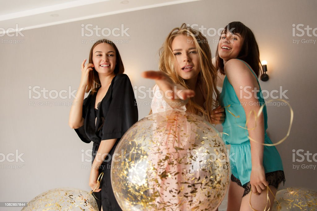 Lovely girls giving an air kiss, while posing at camera. stock photo