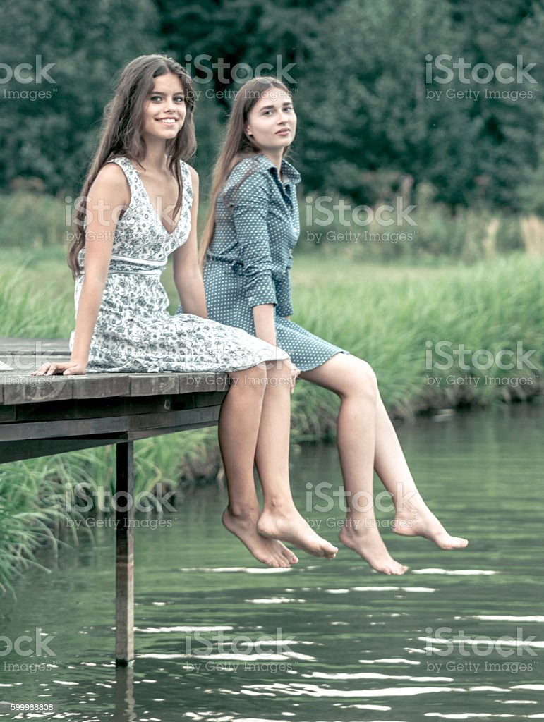 Lovely Girls Sitting On Wooden Footbridge stock photo