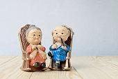 立地の背景を持つ木製のテーブルで一緒に古いソファチェア古典的な素敵な祖父母の人形。