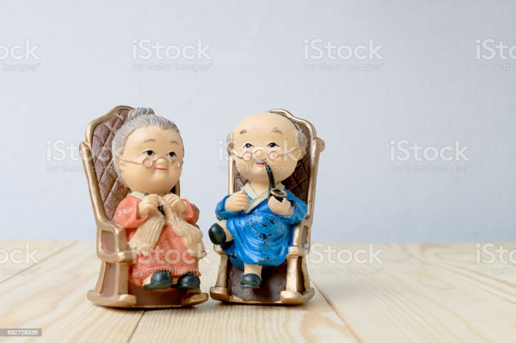 lovely grandparent doll siting old sofa classic chair together on wooden table with background. stock photo