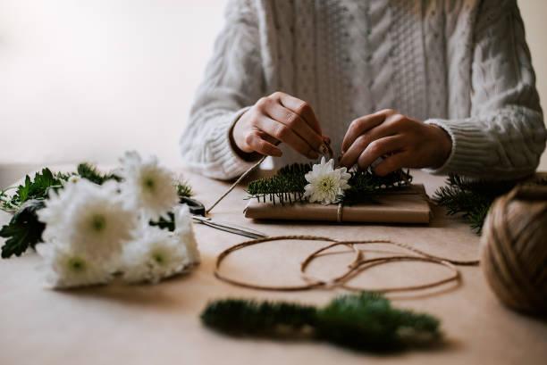schöne handgemachte geschenkverpackung mit naturpapier, seil, tannenzweigen und blume. - weihnachtsideen stock-fotos und bilder