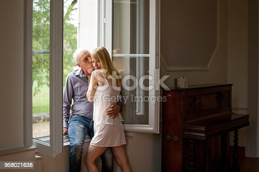 Lovely Happy Couple with Age Difference Hugging near the Window in Their Home. Attractive Blonde Young Woman and Senior Man Embracing Indoor.