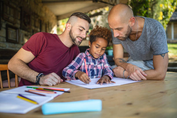 Lovely heterosexual couple doing homework with their adopted daughter Beautiful and lovely gay homosexual couple enjoying their time spent together as a family with their beautiful adopted mixed race daughter. gay couple stock pictures, royalty-free photos & images