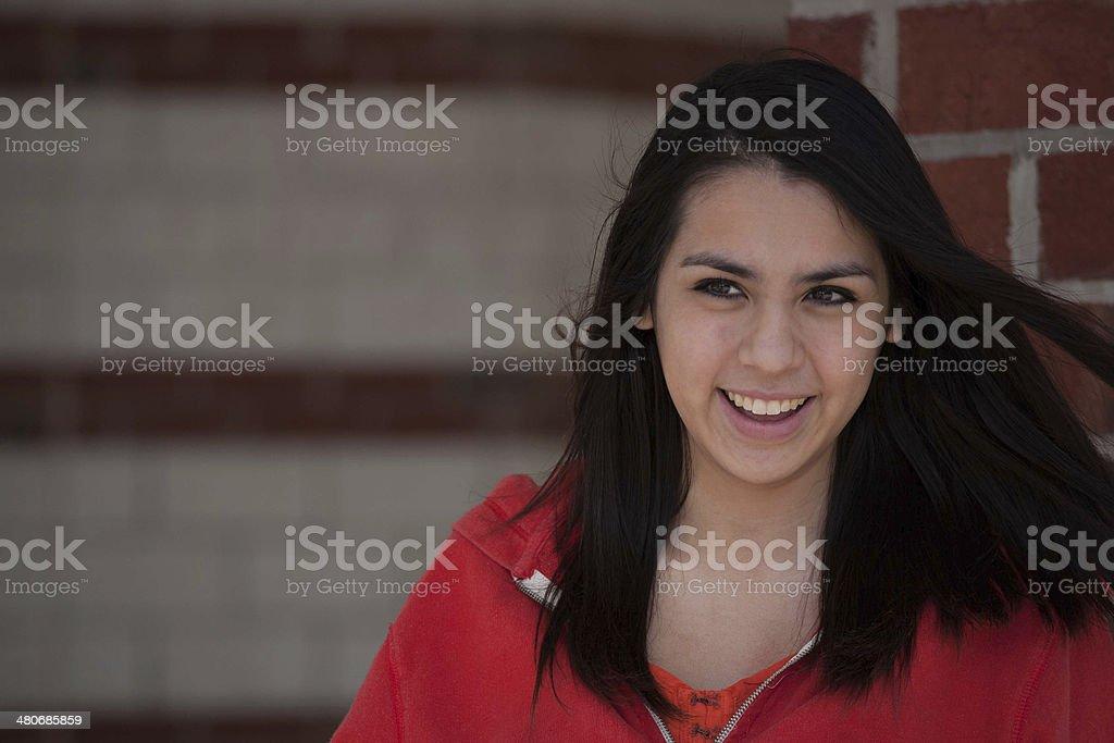 Lovely Hispanic female teenager smiling at school stock photo