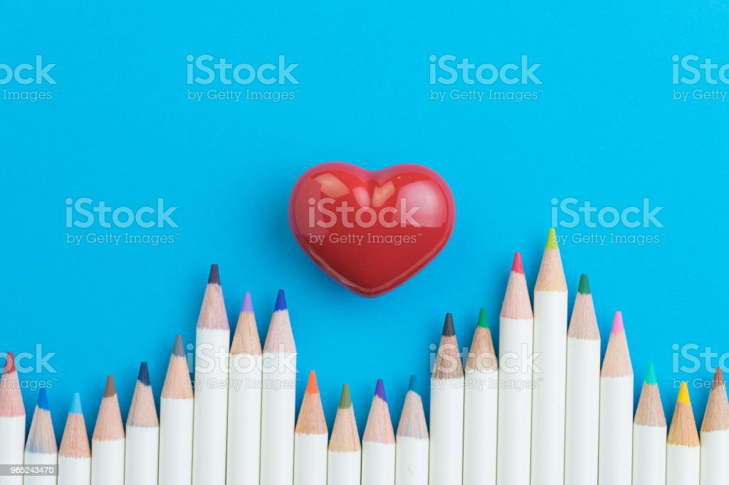 Lovely hobby, adult anti-stress therapy color pencils on vivid blue paper background with red heart at the center, copy space royalty-free stock photo