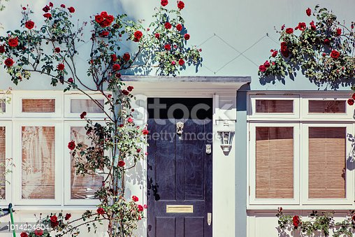 istock Lovely house facade with blue wall and red roses in Notting Hill, London 1014224604
