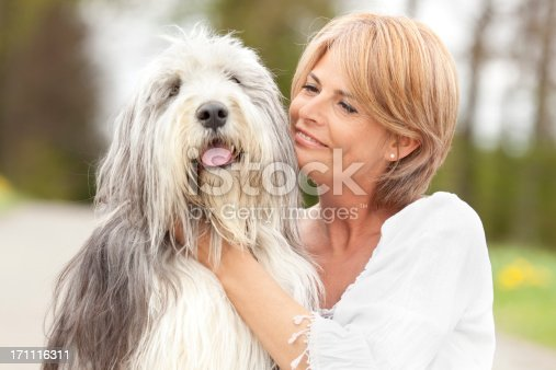 lovely hug between beautiful mature woman and her bearded collie,selective focus