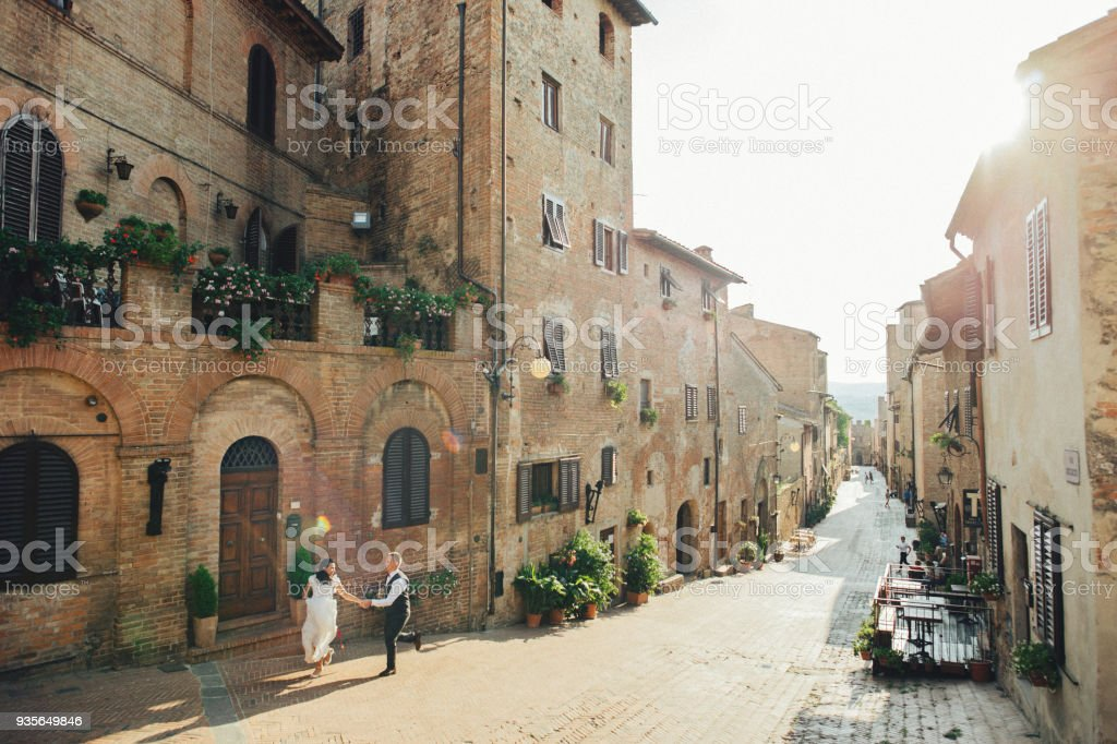 Lovely hugging wedding couple stands before the gates to an old Italian villa stock photo