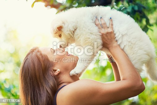 istock Lovely Husky Baby Puppy how Kiss his Female Owner 477778706