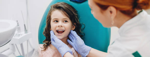 Lovely kid smiling to the doctor while having a teeth surgery at the stomatology stock photo