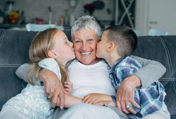 Lovely kids kissing their grandmother Grandmother embracing her cute grandson and granddaughter on the sofa at home. grandson stock pictures, royalty-free photos & images