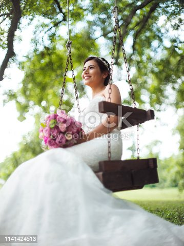 A lovely latin bride sitting on a swing and smiling away.