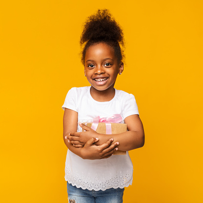 istock Lovely little african girl smiling with present box 1176739980