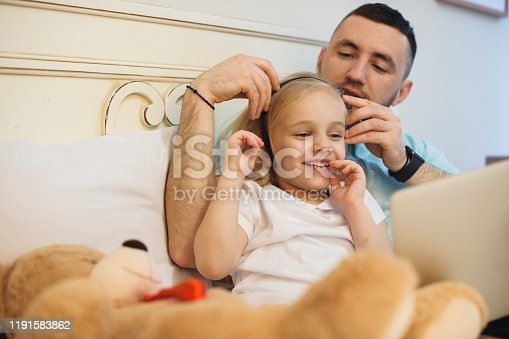 Lovely little blonde girl spending good time with her father in the morning while playing in the bed. Young father arranging hair of his daughter.