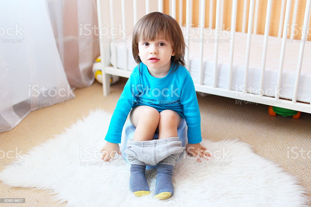 Lovely little boy sitting on potty at home stock photo