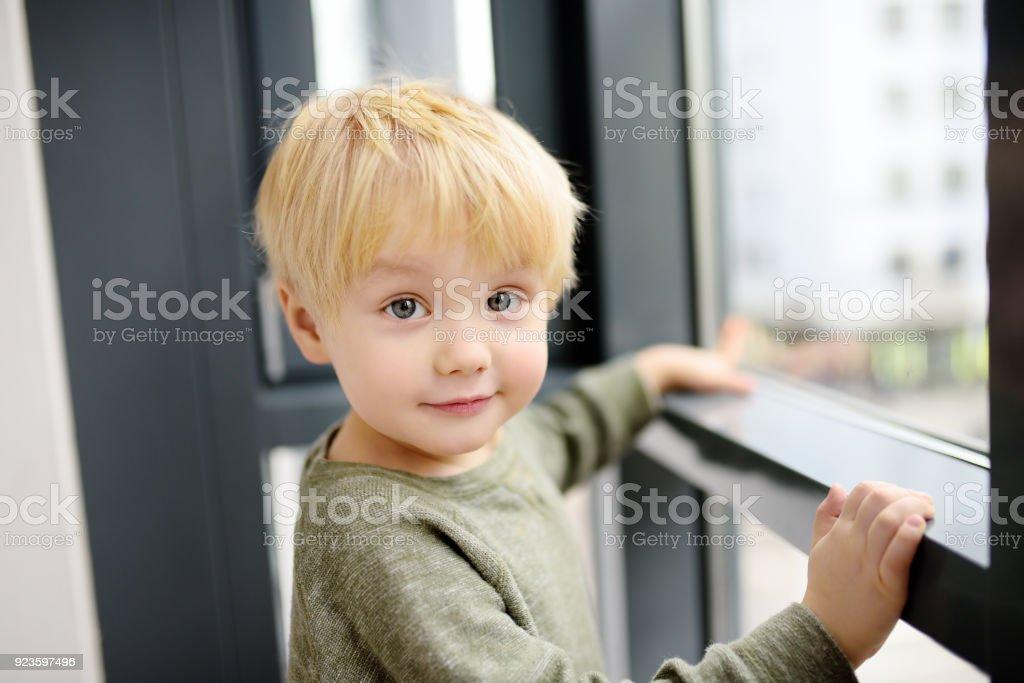 Schöner kleiner Junge sitzt auf dem Fenster in der Nähe von Panoramafenster und nach draußen – Foto