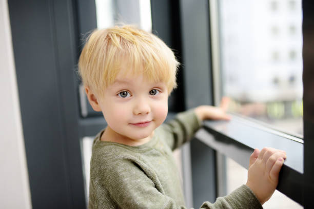 Lovely little boy sitting on the window near panoramic window and looking outside stock photo