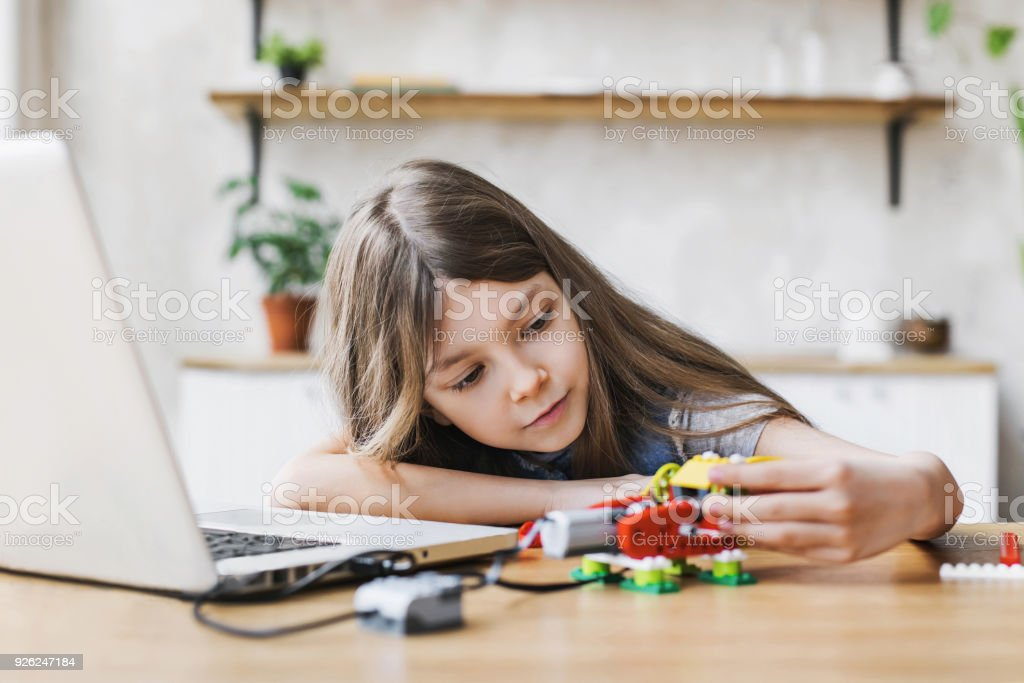 Lovely little girl builds robot after school stock photo
