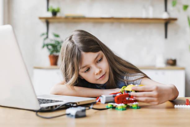 Lovely little girl builds robot after school stock photo