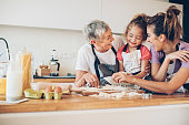 Three generations of women preparing cookies together in a domestic kitchen, with copy space