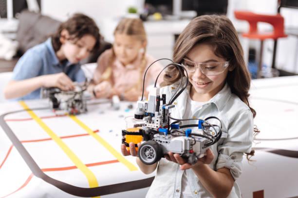 Lovely little girl holding robot at school stock photo