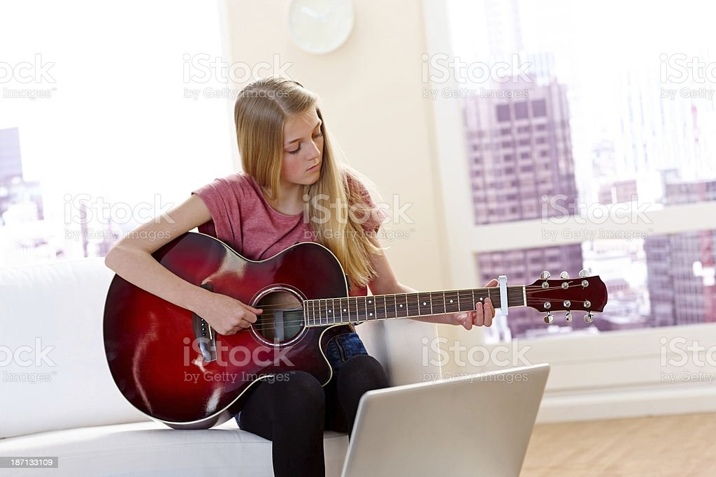 Lovely little girl playing guitar at home royalty-free stock photo