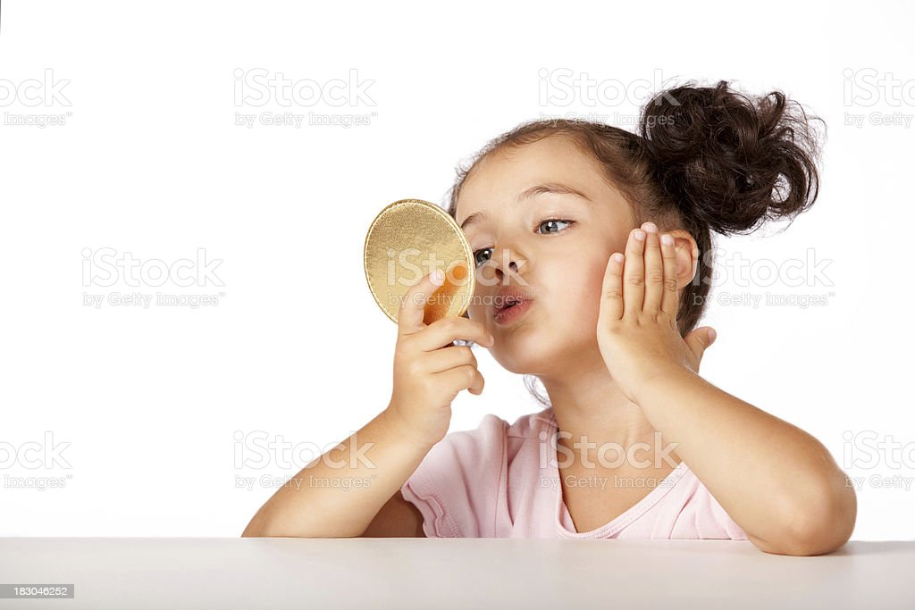 Lovely little girl smartening up at a mirror royalty-free stock photo