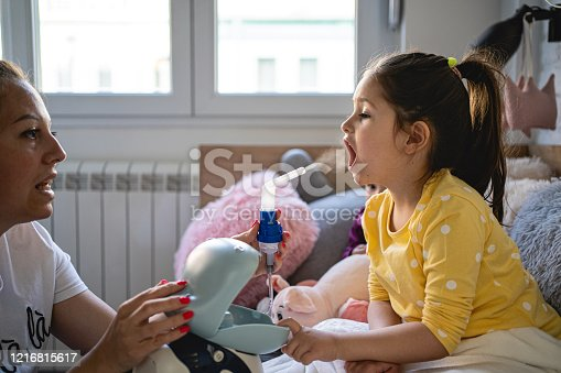 Caring mother helping her daughter to do inhalation with a steam nebulizer in child bedroom