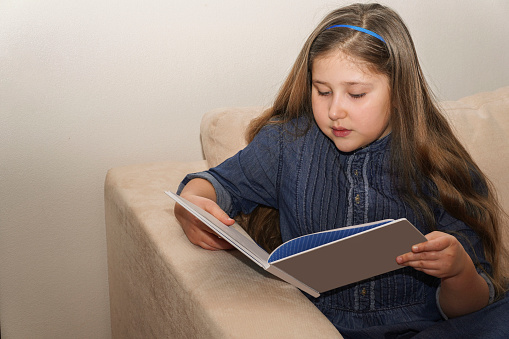 Lovely little long hair girl wearing on a blue denim dress reading book on light background. Childhood, school and education concept. Copyspace.