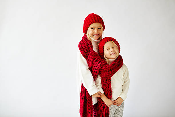 lovely little sisters wearing warm knit hats and scarf - red hutgesellschaft stock-fotos und bilder