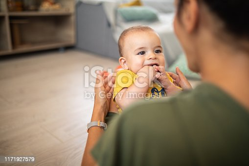Young woman holding her baby boy in lap while sitting on bed at home