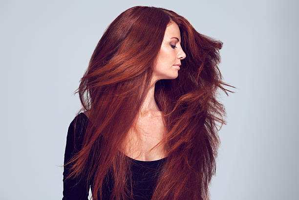 Lovely luscious locks Studio shot of a young woman with beautiful red hair posing against a gray background straight hair stock pictures, royalty-free photos & images