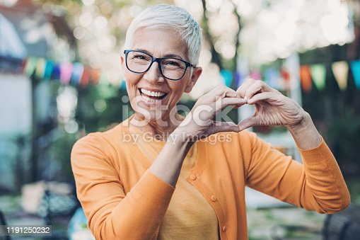 Portrait of a smiling senior woman gesturing outdoors