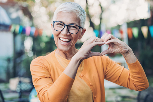 Lovely mature woman making heart shape with hands