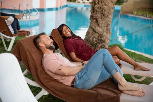 liebes gemischtes paar genießen die entspannung des hotelgartens und des pools - hochzeitsreise dubai stock-fotos und bilder