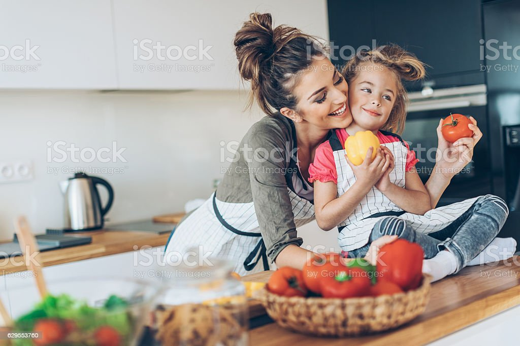 Lovely mother and daughter in the kitchen stock photo
