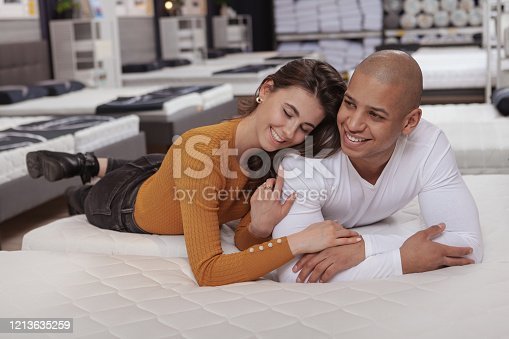 Happy multiethnic couple laughing, enjoying shopping together for a new bed for their new home