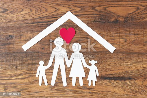 Lovely paper family with house on dark wooden background top view. Happy family, insurance concept.