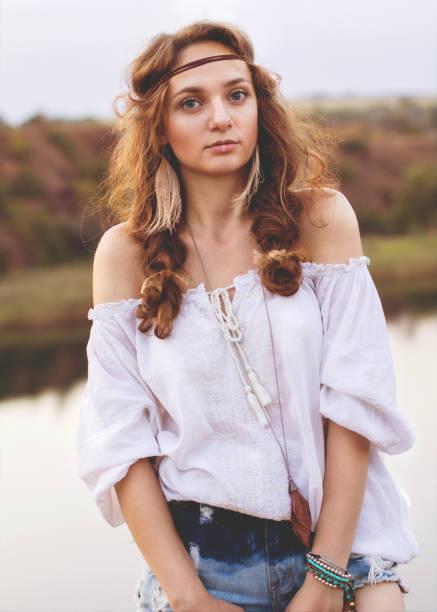 schönes portrait eines mädchens in einem boho-stil auf dem hintergrund eines sees. weichen warmen vintage fotofarbe. - hippie kleider stock-fotos und bilder