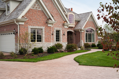 Lovely red brick custom home with stamped concrete driveway in residential neighborhood.