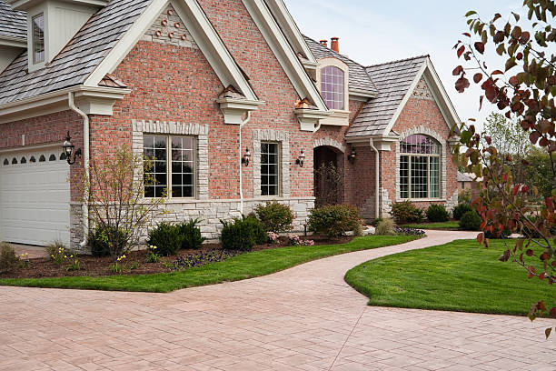 lovely red brick upscale home with concrete driveway. - stamper stock photos and pictures