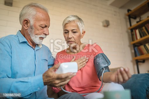 Beautiful and lovely looking senior couple measuring blood pressure to one another at home.