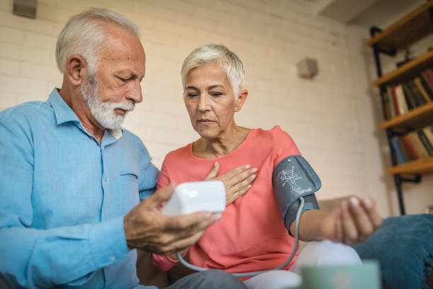 Lovely senior couple measuring blood pressure Beautiful and lovely looking senior couple measuring blood pressure to one another at home. woman taking pulse stock pictures, royalty-free photos & images