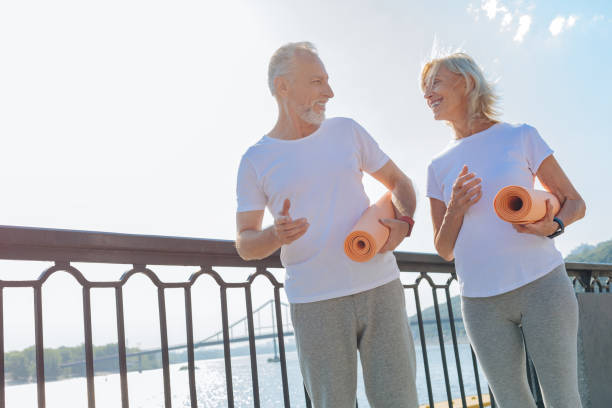 Lovely senior couple walking with yoga mats stock photo
