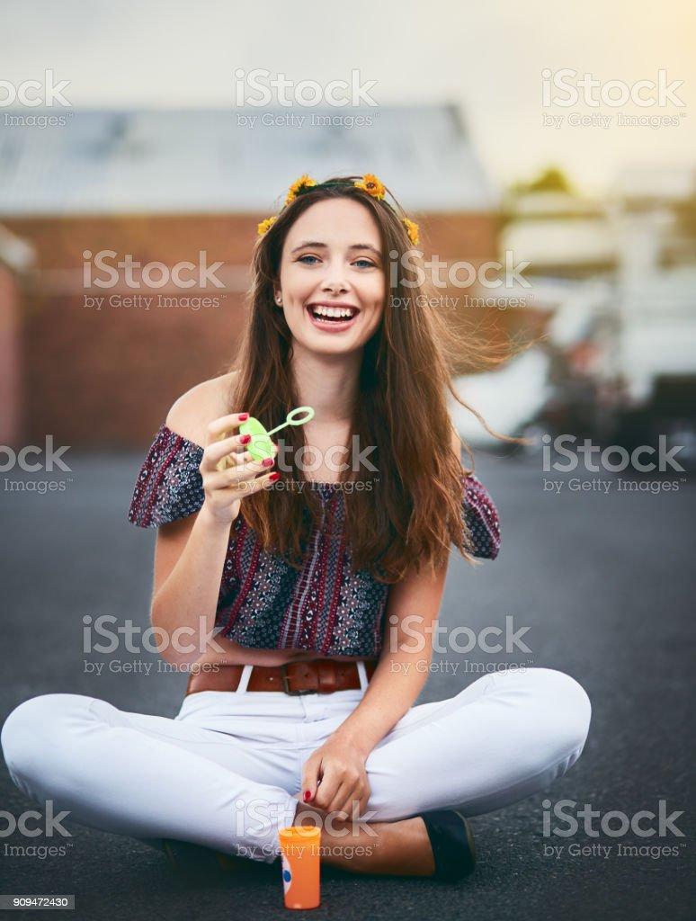 Belle fille sereine avec des fleurs dans les cheveux souffle bulles, rire - Photo
