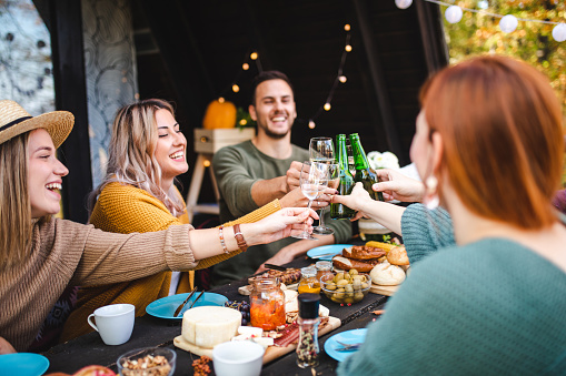 Charming group of young friends toasting with wine and beer during their outdoor brunch after long time no see