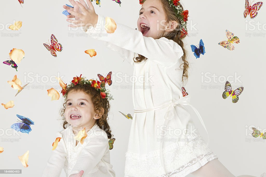 Lovely sisters playing with petals and butterflies royalty-free stock photo