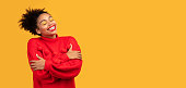 Good Girl. Cute peaceful afro girl hugging her shoulders isolated on yellow wall, tilts her head, panorama, copyspace